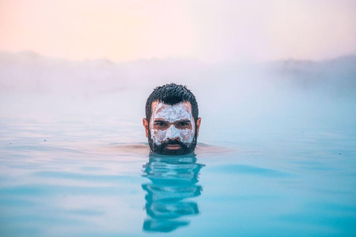 Ein Mann mit einer Maske aus Schlamm und Kieselerde genießt das warme Wasser des Thermalfreibads Bláa ...