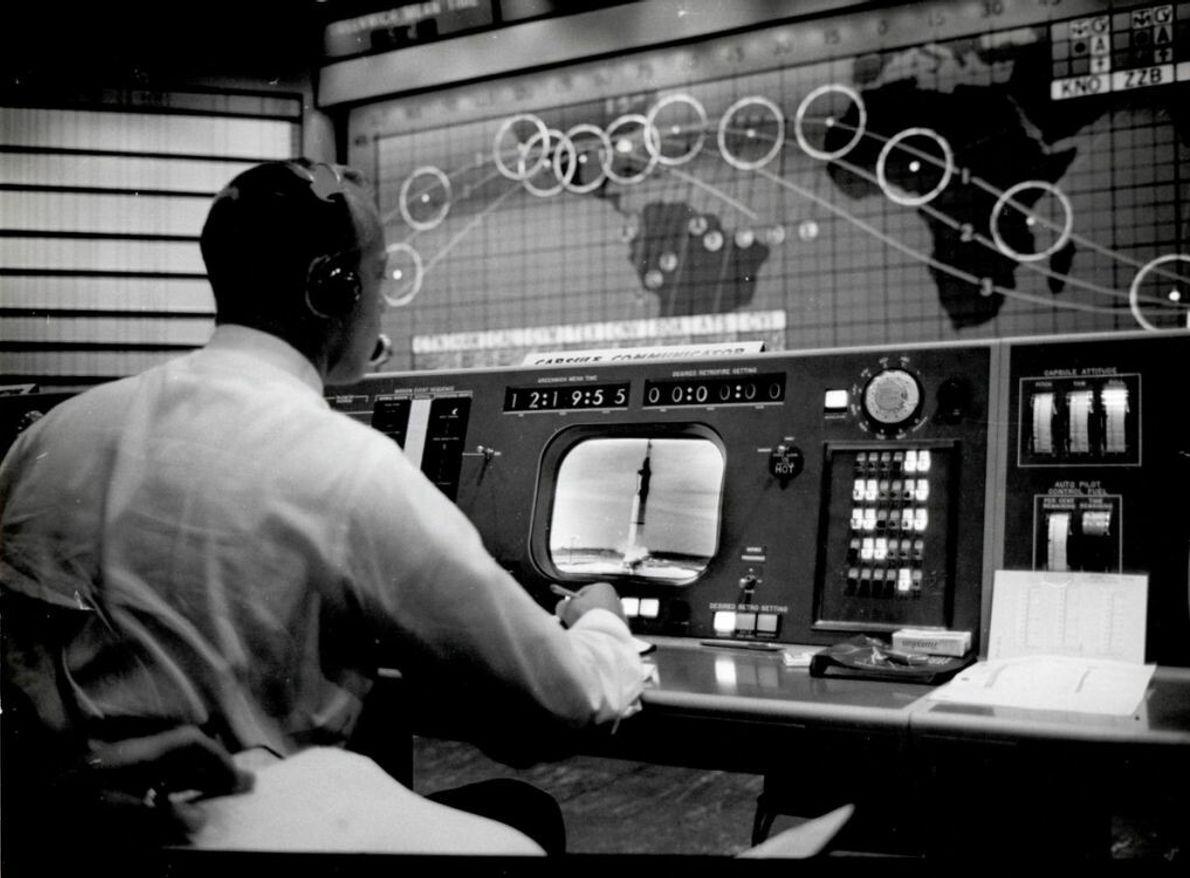 "Der Mercury-Astronaut Alan Shepard arbeitet als Kapselkommunikator (""capcom"") an seiner Konsole in der Flight Control Area. ..."