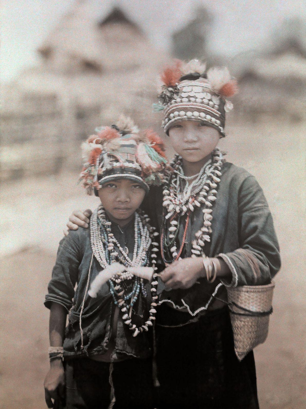 Zwei Jungen der Shan in Myanmar tragen Hüte, die mit Quasten und Stoffbüscheln verziert sind.