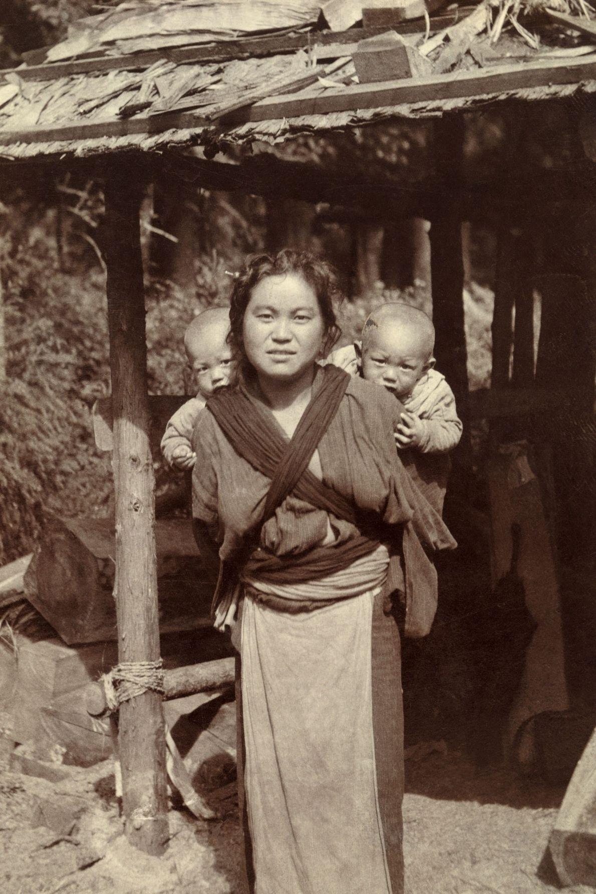 Eine japanische Mutter trägt ihre Zwillinge mit einem Tragetuch auf dem Rücken.