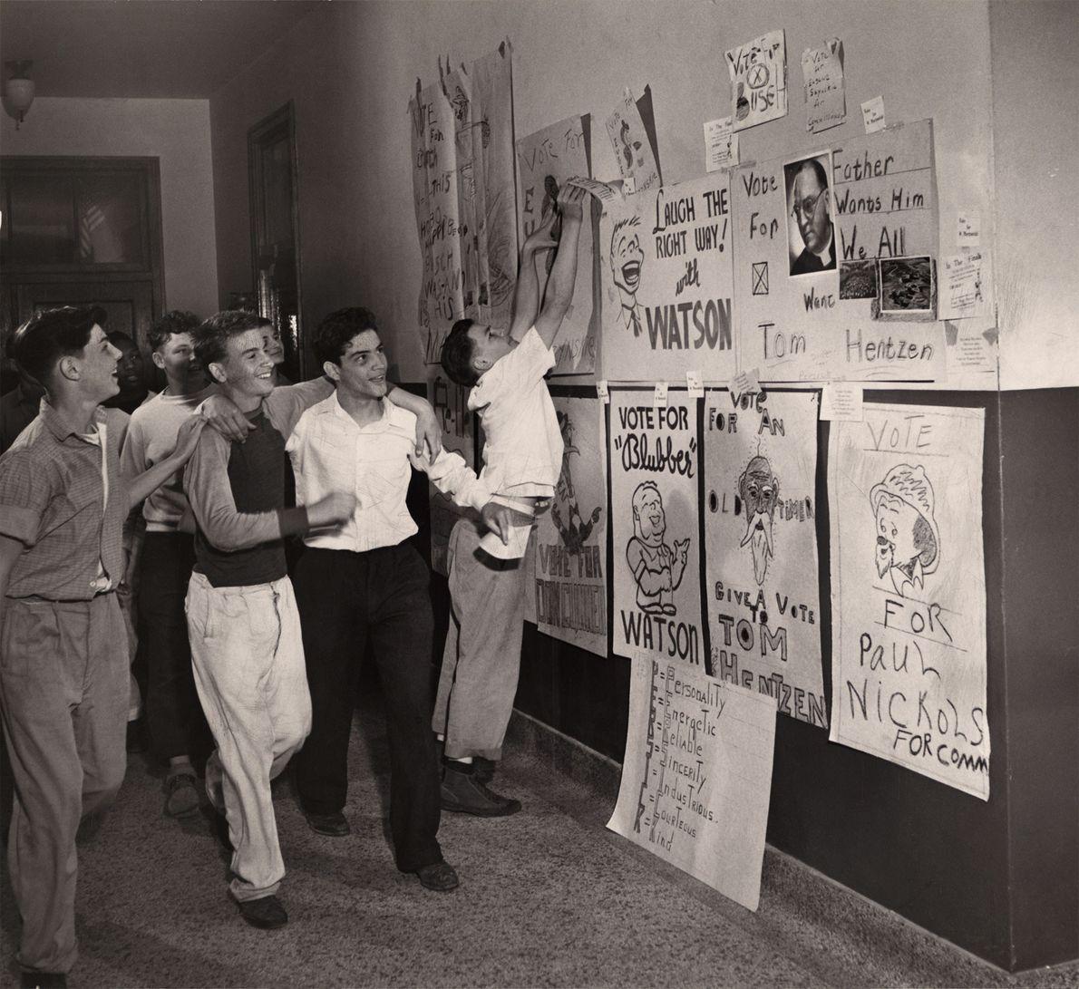 Ein paar Jungs sehen sich die Kampagnenposter für eine bevorstehende Wahl zum Klassensprecher an.