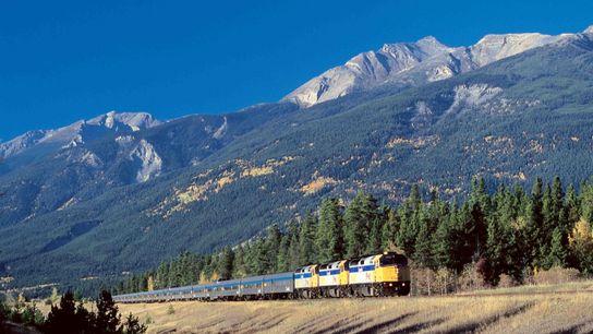 Ein Via Rail-Zug fährt durch die atemberaubende Landschaft der kanadischen Rocky Mountains.