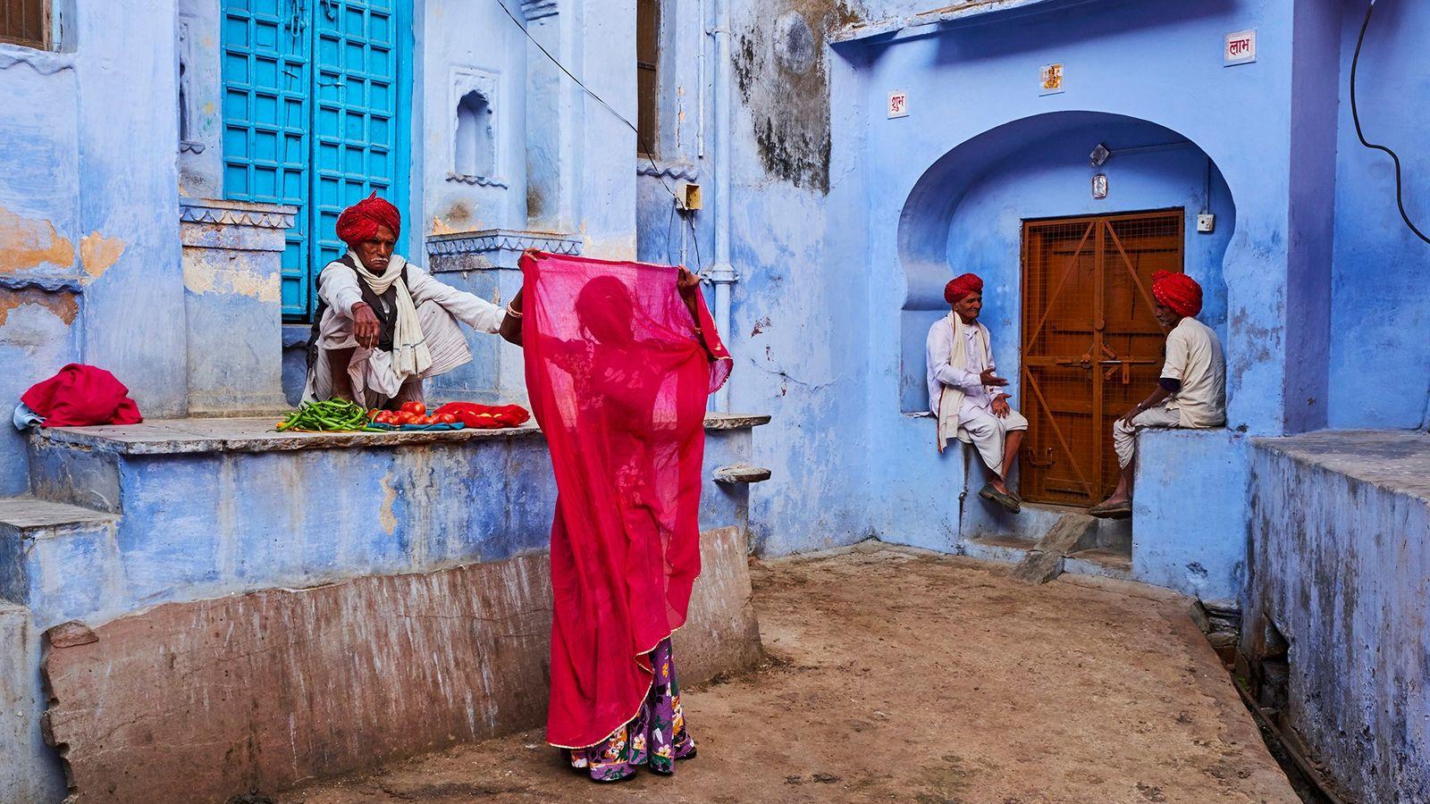 """In Jodhpur, Rajasthan, kontrastiert der karmesinrote Dupatta einer Frau mit den pastellfarbenen Wänden der """"blauen Stadt""""."""