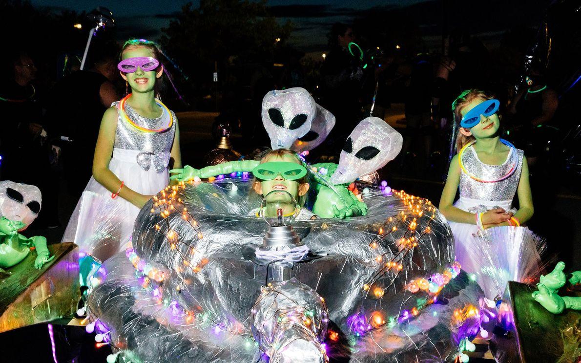 Drei Kinder in Alienkostümen bereiten sich auf ihren Auftritt bei der 2018 UFO Light Parade in ...