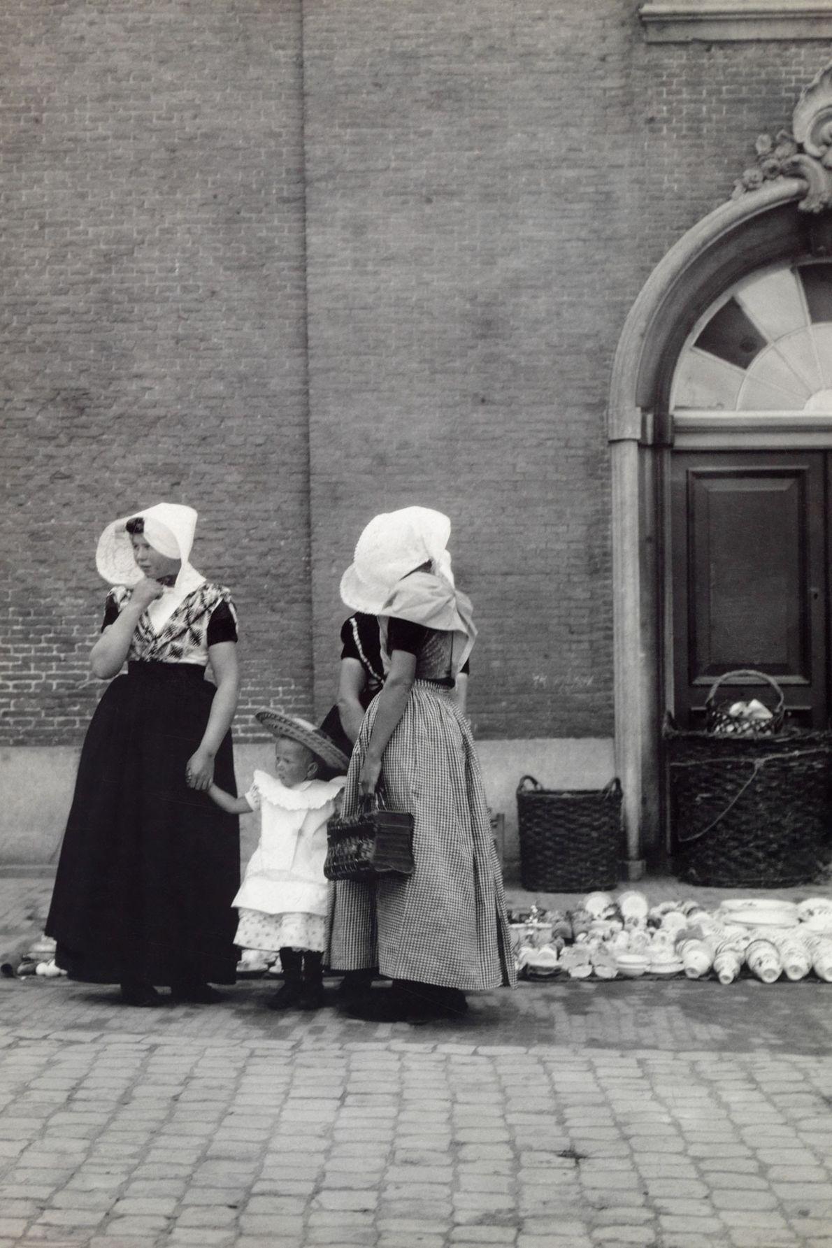 Eine Magd und ihre Herrin halten ein junges Kind an den Händen, während sie auf einer ...
