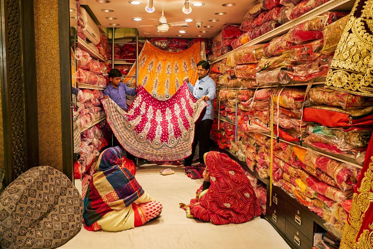 Women shop for saris in a store in Jaipur stacked floor-to-ceiling with textiles. Sari shopping can ...