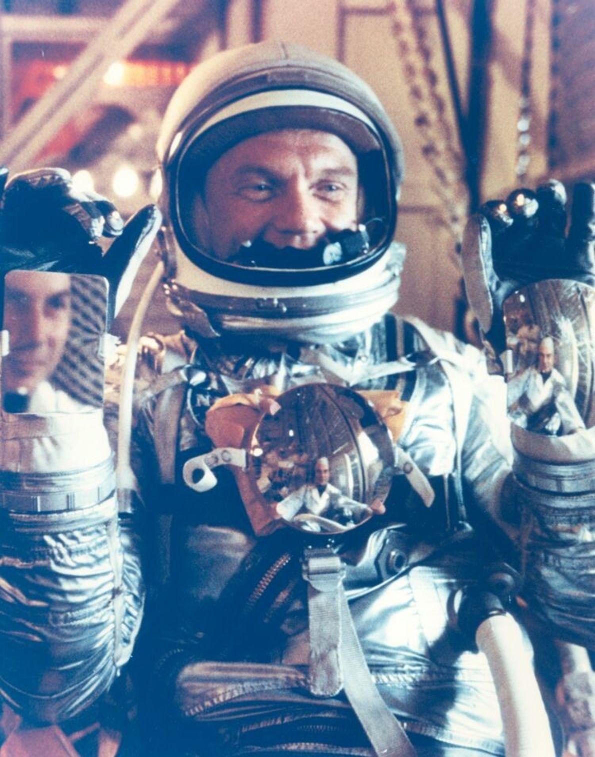 John Glenn posiert in seinem Mercury-Anzug. Die Spiegel sollten es den Astronauten in ihren klobigen Anzügen ...