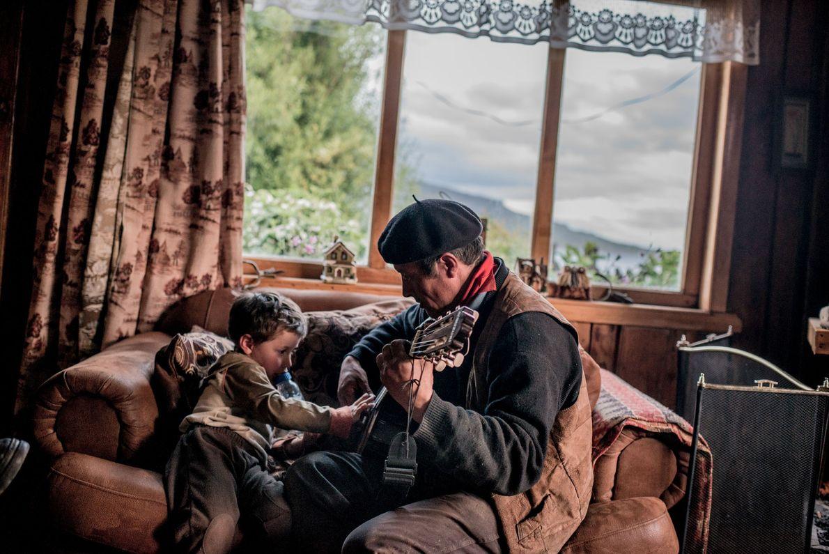 In Patagonien, Chile, spielt ein Cowboy für seinen Enkel auf der Gitarre. 2014.