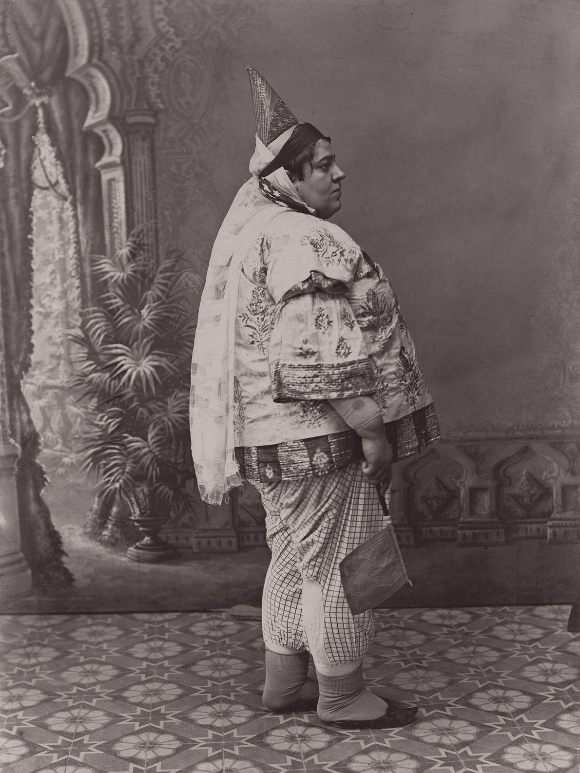 Eine Frau in Kleidung aus Satin und Seide steht in einem Innenhof in Tunesien. Ihr spitz ...