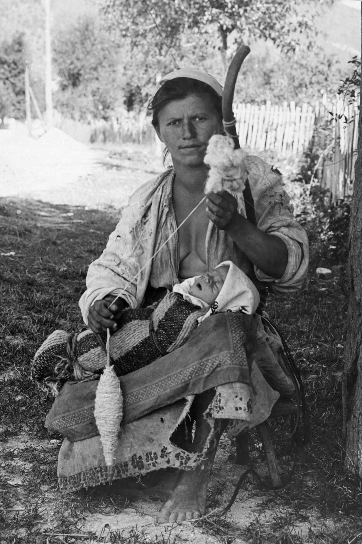 Eine ungarische Frau spinnt Wolle, während ihr Baby auf ihrem Schoß schläft.