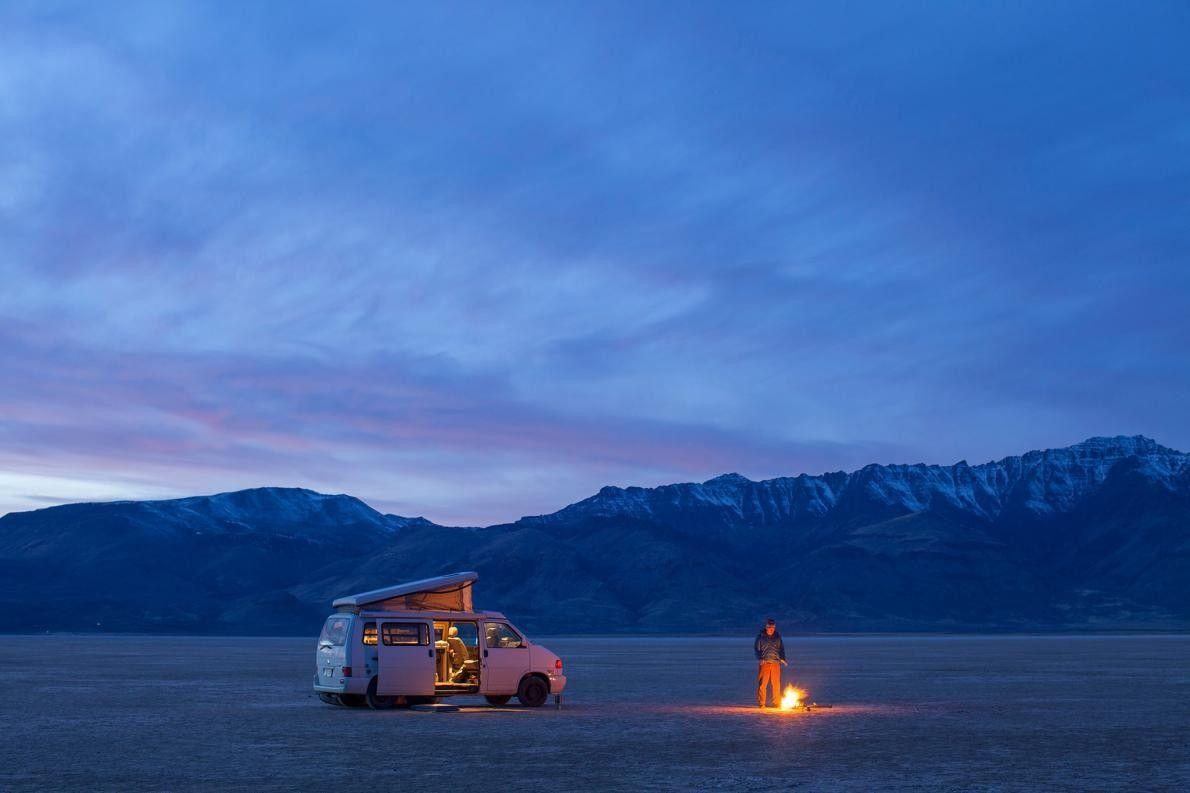 Camper steht an einem Feuer