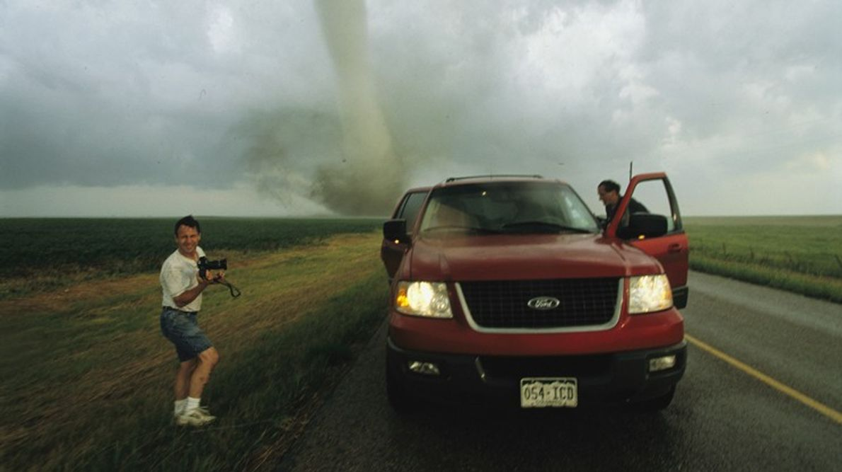 Ein Tornadojäger mit einer Kamera posiert für eine Aufnahme, während sein Partner in den Truck klettert. ...