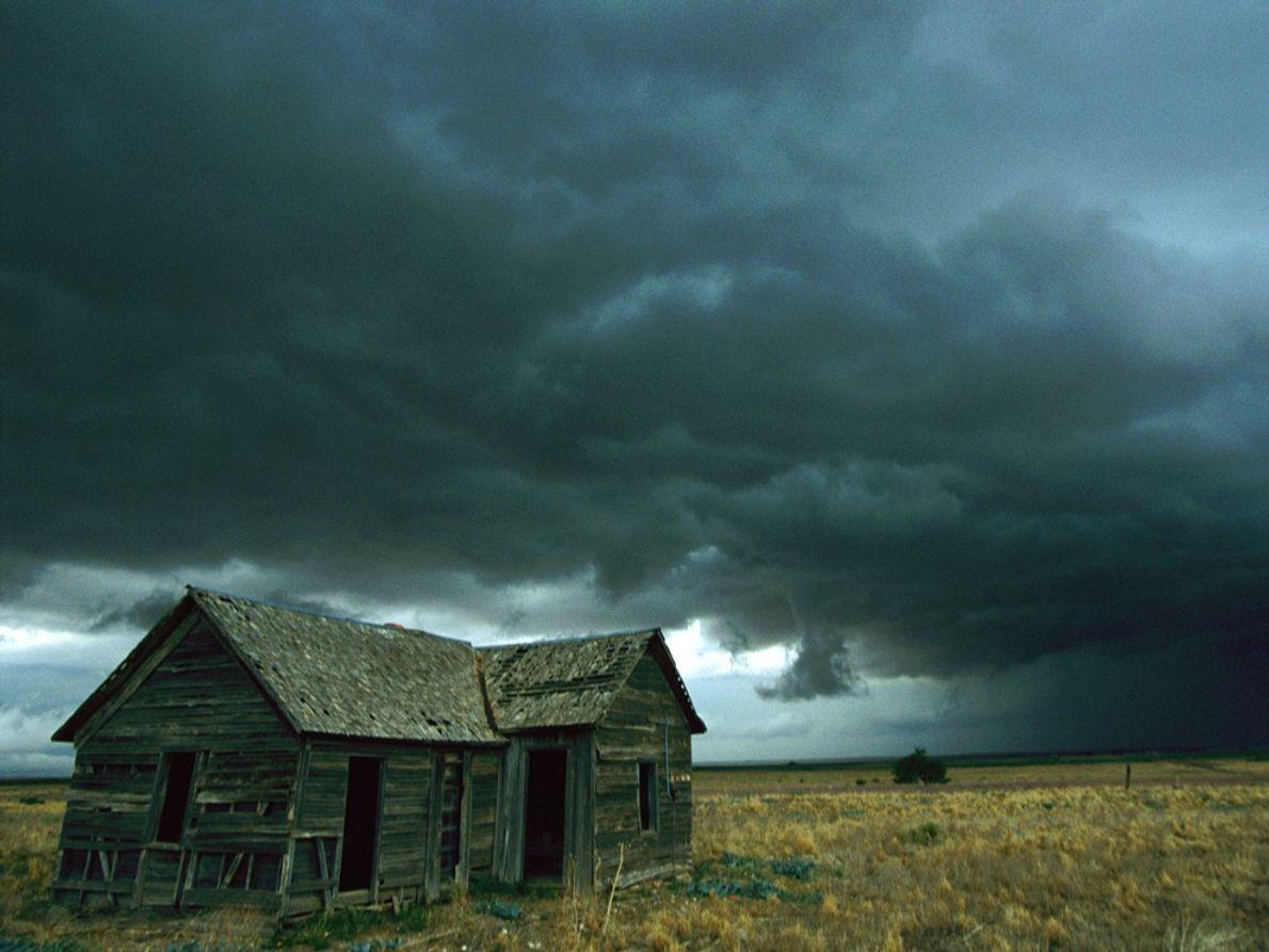 Dunkle Wolken hängen über einem verfallenen Haus im Mittleren Westen der USA. Sie verheißen einen möglichen ...