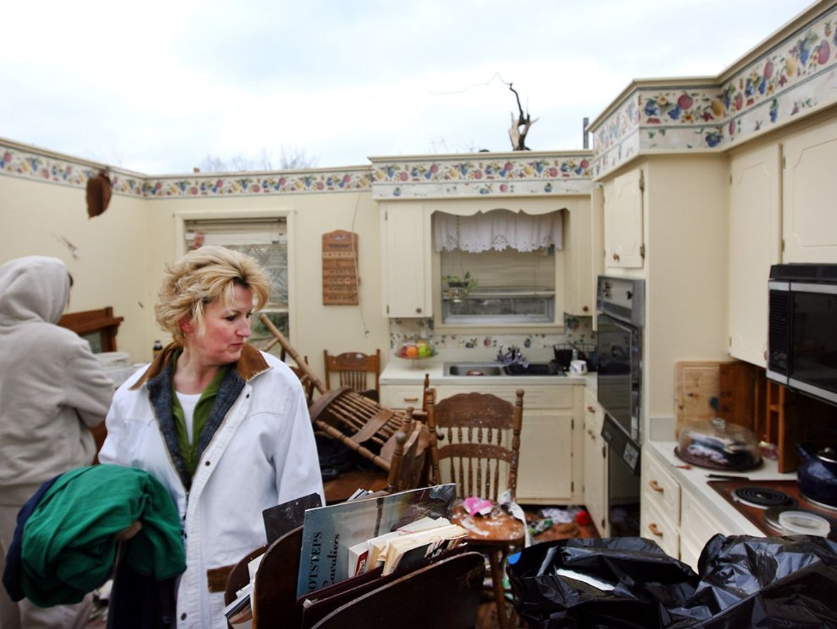A woman searches the wreckage of her mother's house in Arkansas after a tornado removed the ...