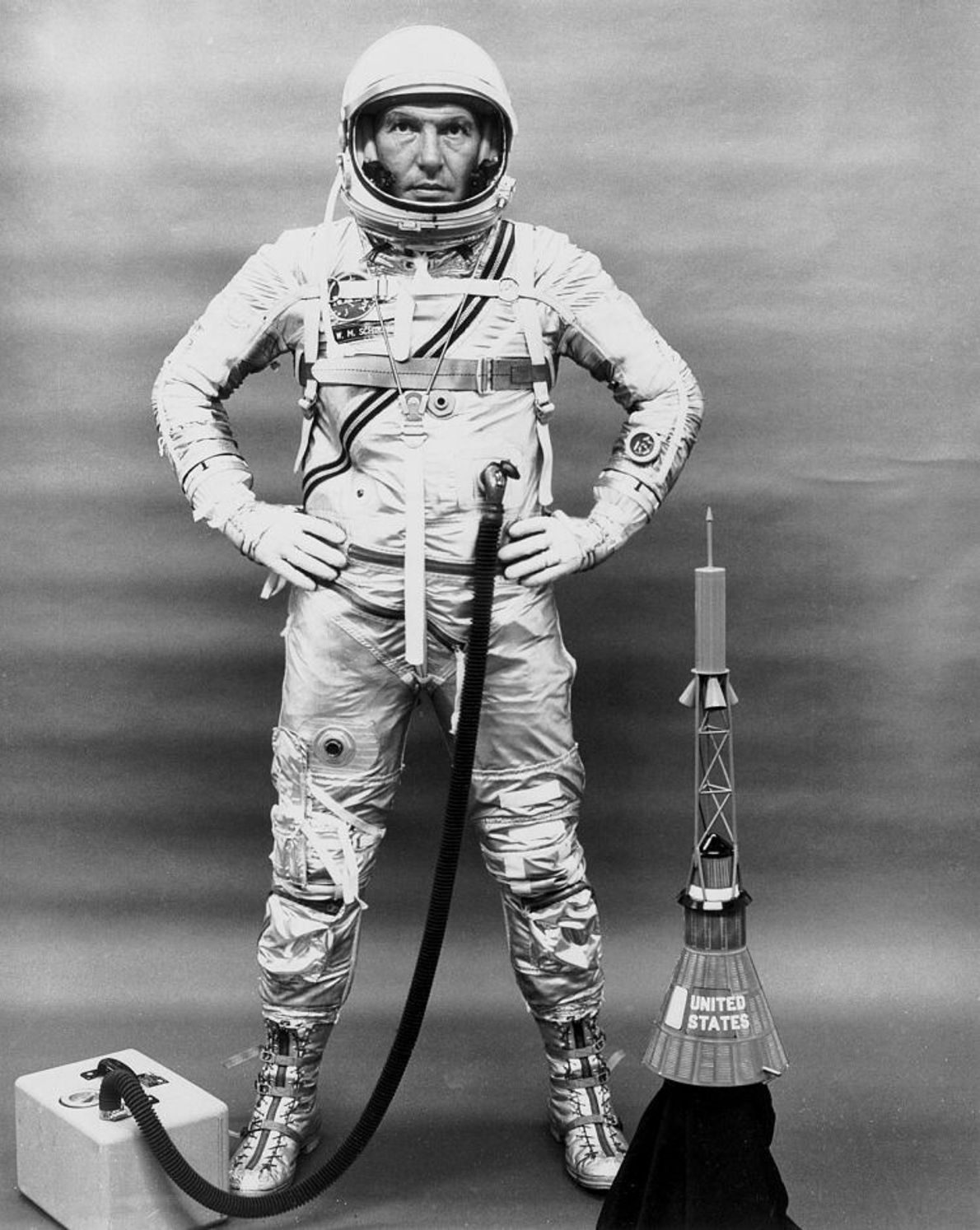 Wally Schirra posiert mit seinem Anzug, einem tragbaren Sauerstofftank und einem Modell der Mercury-Kapsel. Schirras war ...