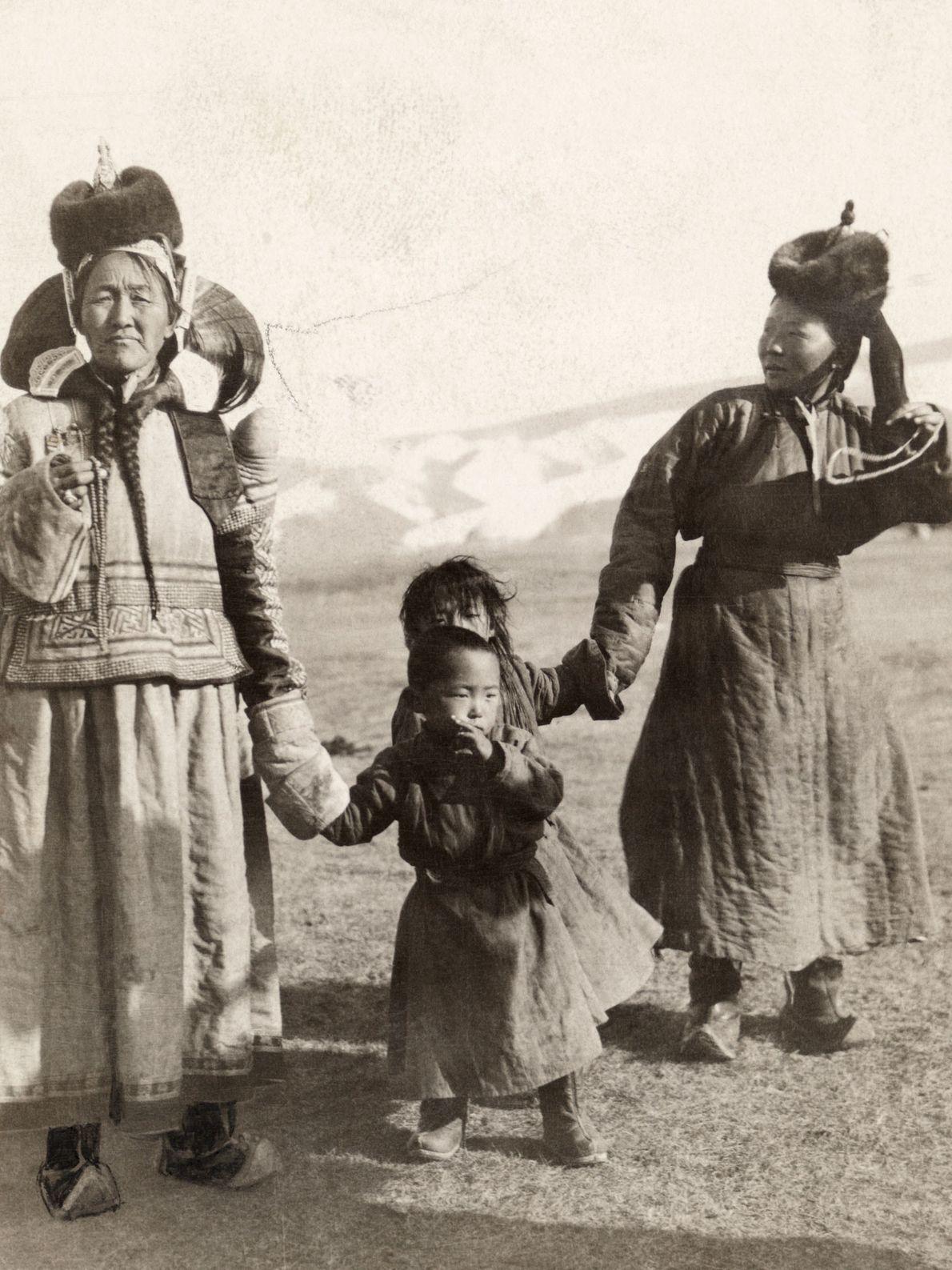 Im Norden der Mongolei laufen zwei Frauen Hand in Hand mit Kindern.