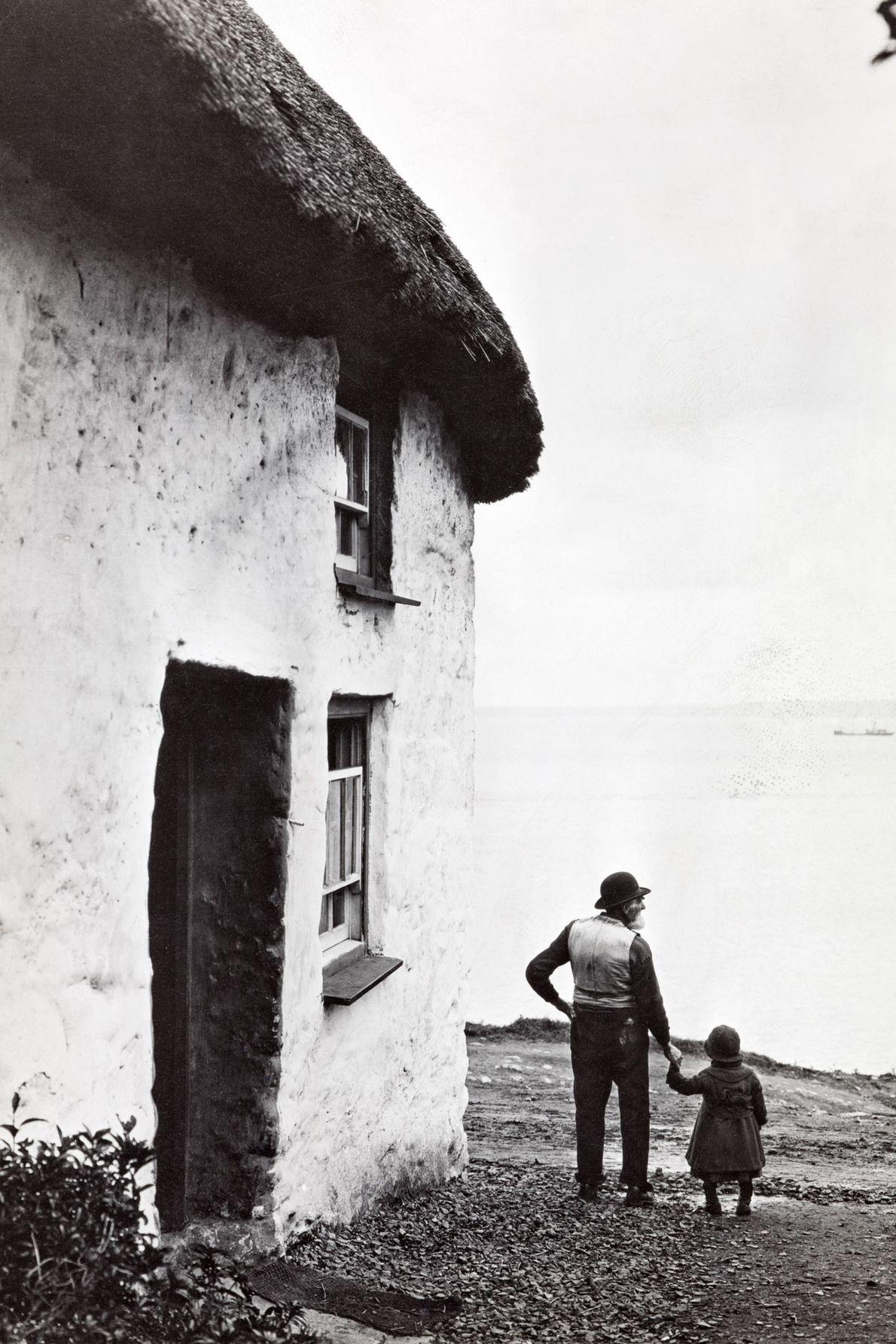 Ein Großvater und seine Enkelin an der Küste von Cornwall blicken Hand in Hand zum Meer. ...
