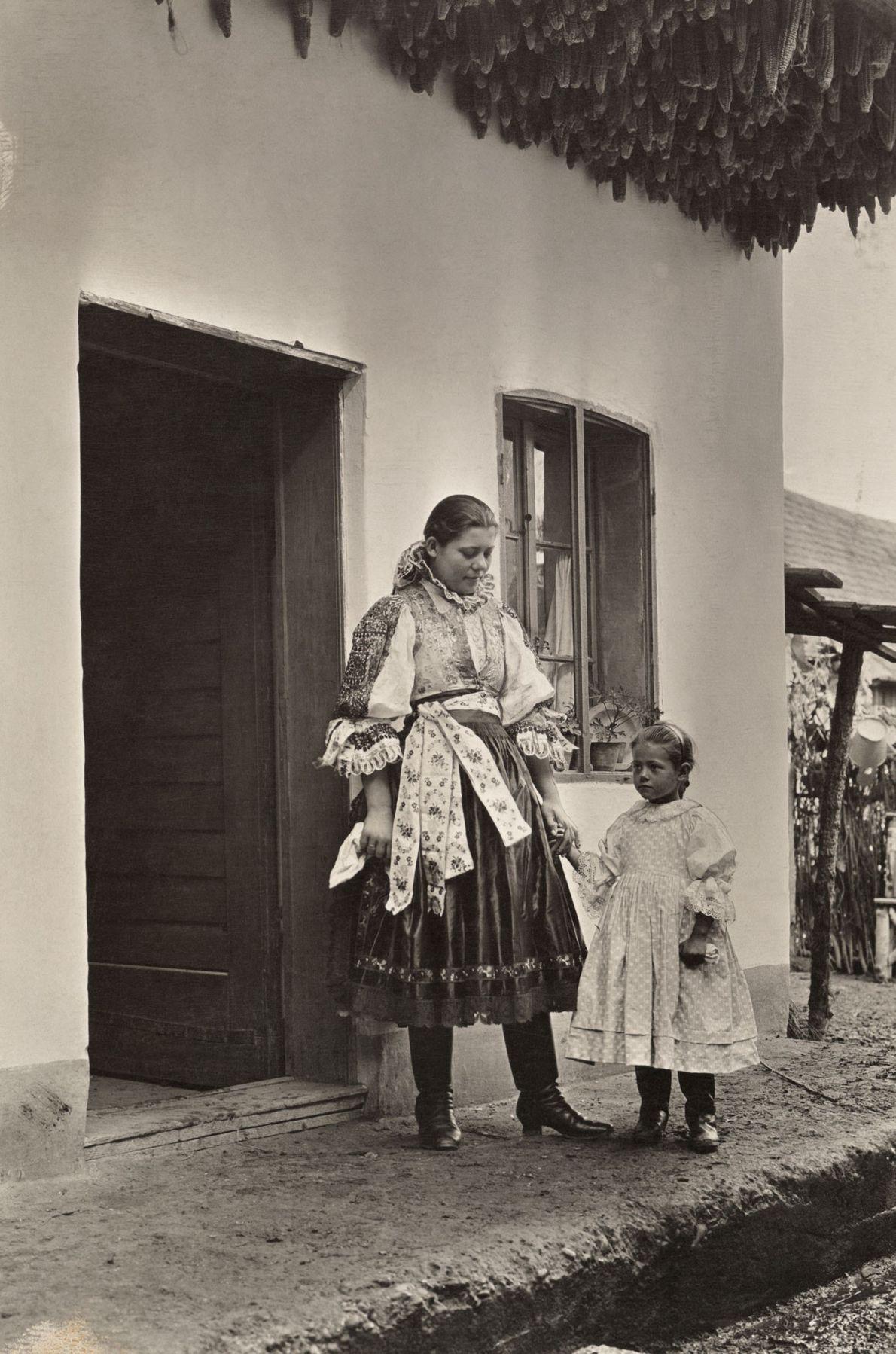 Eine Mutter und ihr Kind stehen auf ihrer Veranda unter zum Trocknen aufgehängten Maiskolben in Postyen, ...
