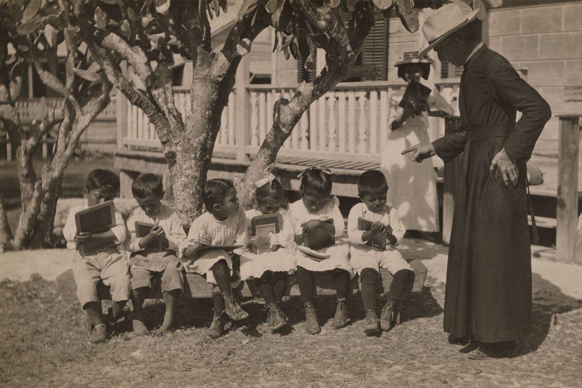 Schüler sitzen im Freien auf einer Bank und schreiben ihre Lektionen auf kleine Tafeln.