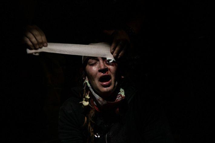 Eine Demonstrantin erhält auf dem Parkplatz eines Kaufhauses Erste Hilfe, nachdem ein Gummigeschoss der Polizei die ...