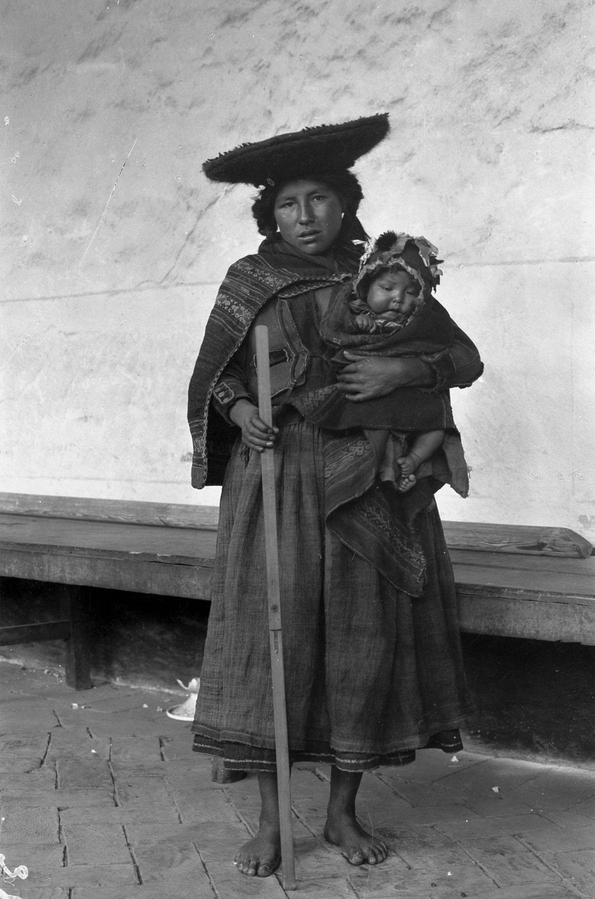 Eine Mutter hält in einem Arm ihr Kind und in der anderen Hand einen Zollstock, während ...
