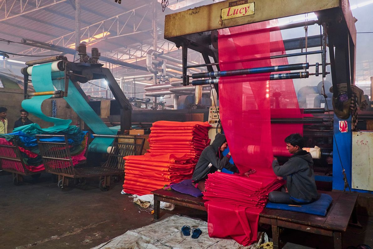 Textile factory workers in Rajasthan's Saree Factory remove chiffons from giant machine looms. The fabrics are ...