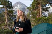 Eine Frau trinkt morgens auf einem Campingplatz in Kalifornien einen Kaffee (Archivbild).
