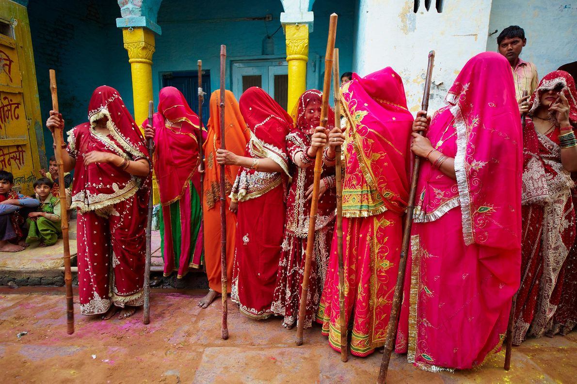 During the Holi festival in Uttar Pradesh, India, women wear traditional red saris and brandish bamboo ...