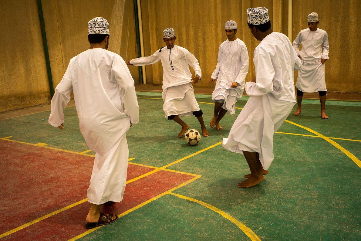 In Al Seeb im Oman spielen junge Männer in ihren traditionellen Kandoras Indoor-Fußball.