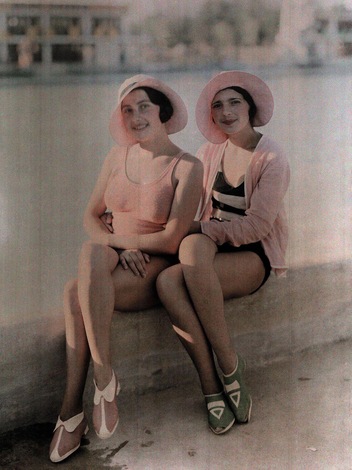 Im rumänischen Bukarest sitzen zwei Mädchen in Badeanzügen mit farblich passenden Hüten in der Sonne.