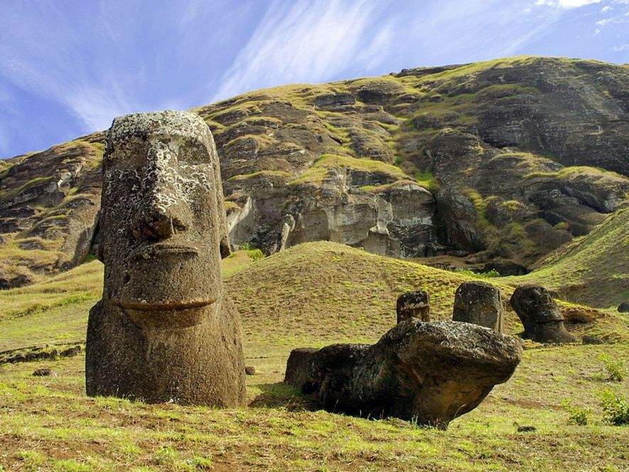 Riesige Moai ragen aus den Wiesen an einem erloschenen Vulkan auf der Osterinsel auf.