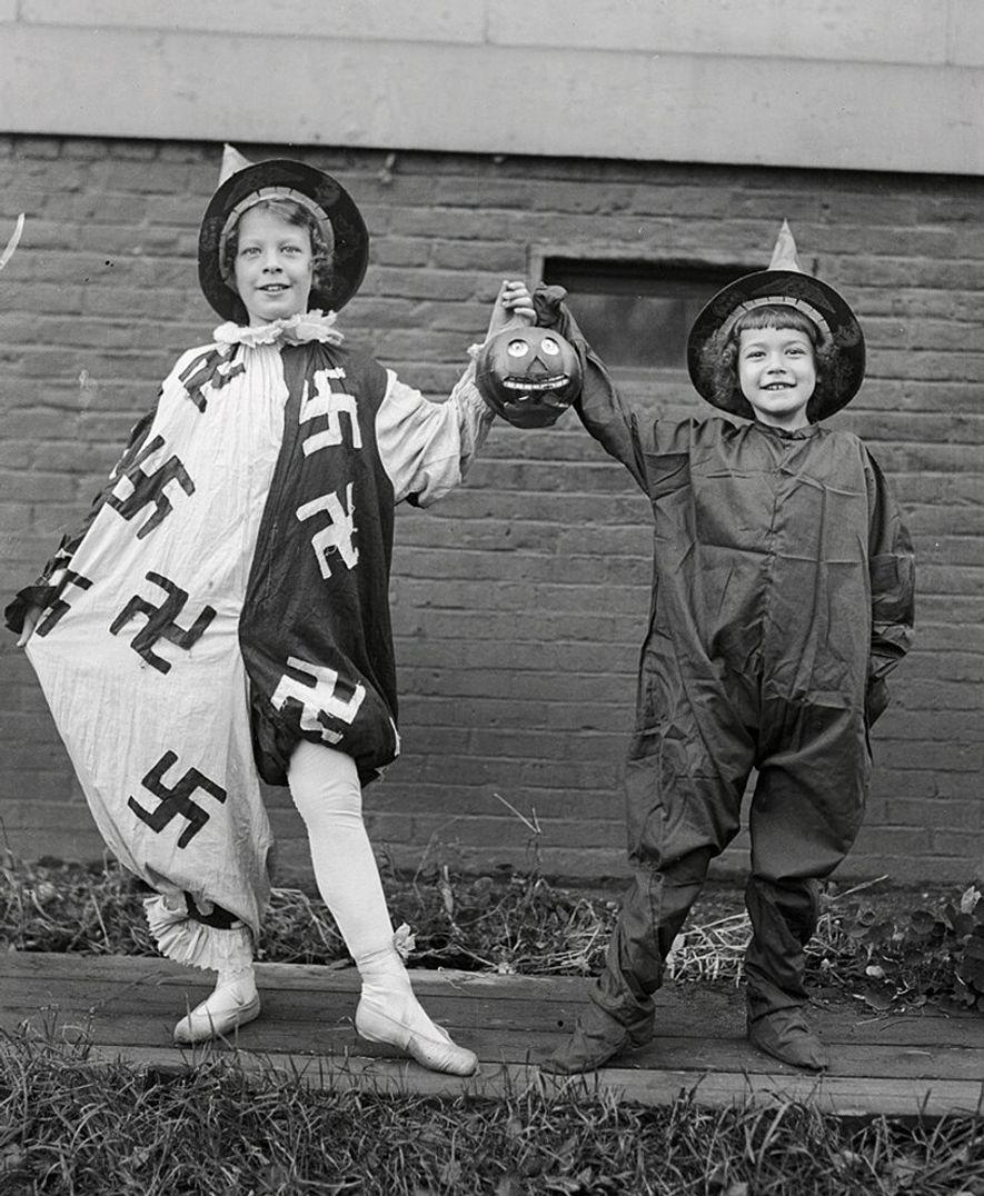 Zwei kostümierte Mädchen auf dem Weg zu einer Tanzveranstaltung lächeln am 25. Oktober 1918 in die ...