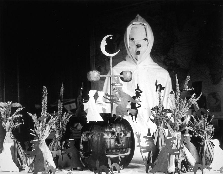 Ein Mensch in einem Geisterkostüm steht vor einem Tisch mit Halloweendekoration in einer ländlichen Schule in ...