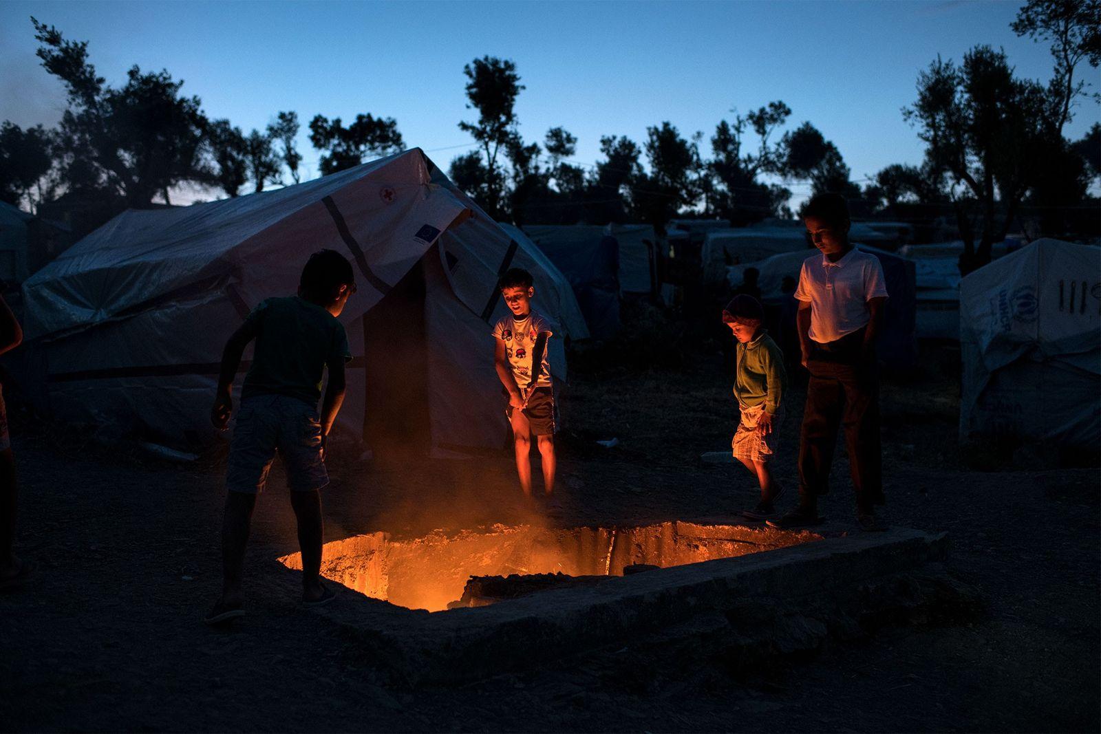 Flüchtlingskinder stehen an einer Grube mit brennendem Müll. Das Feuer soll die Mücken und Insekten fernhalten, ...