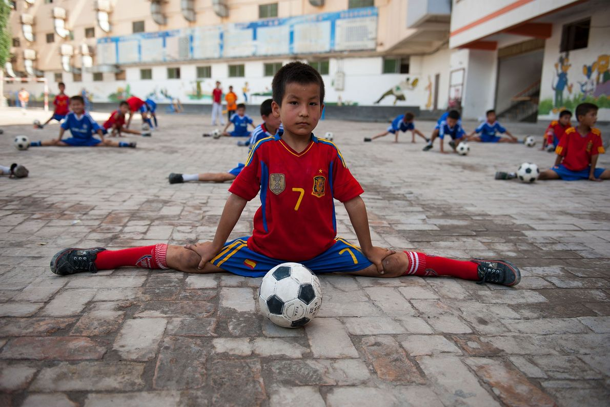 Ein Junge dehnt sich vor seinem Fußballtraining in der chinesischen Provinz Xinjiang, 2001.