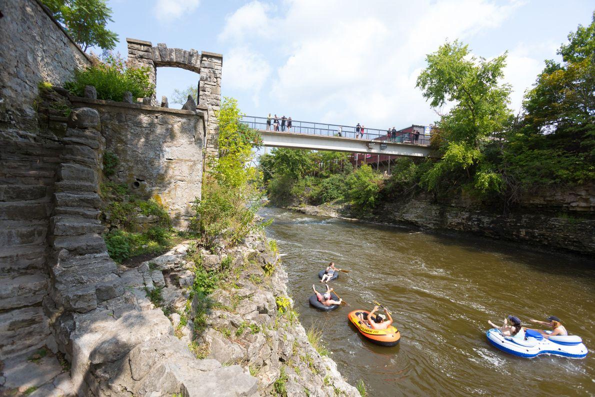 Auf dem Grand River treiben Menschen auf großen Reifen an den Templin Gardens in Fergus vorbei.
