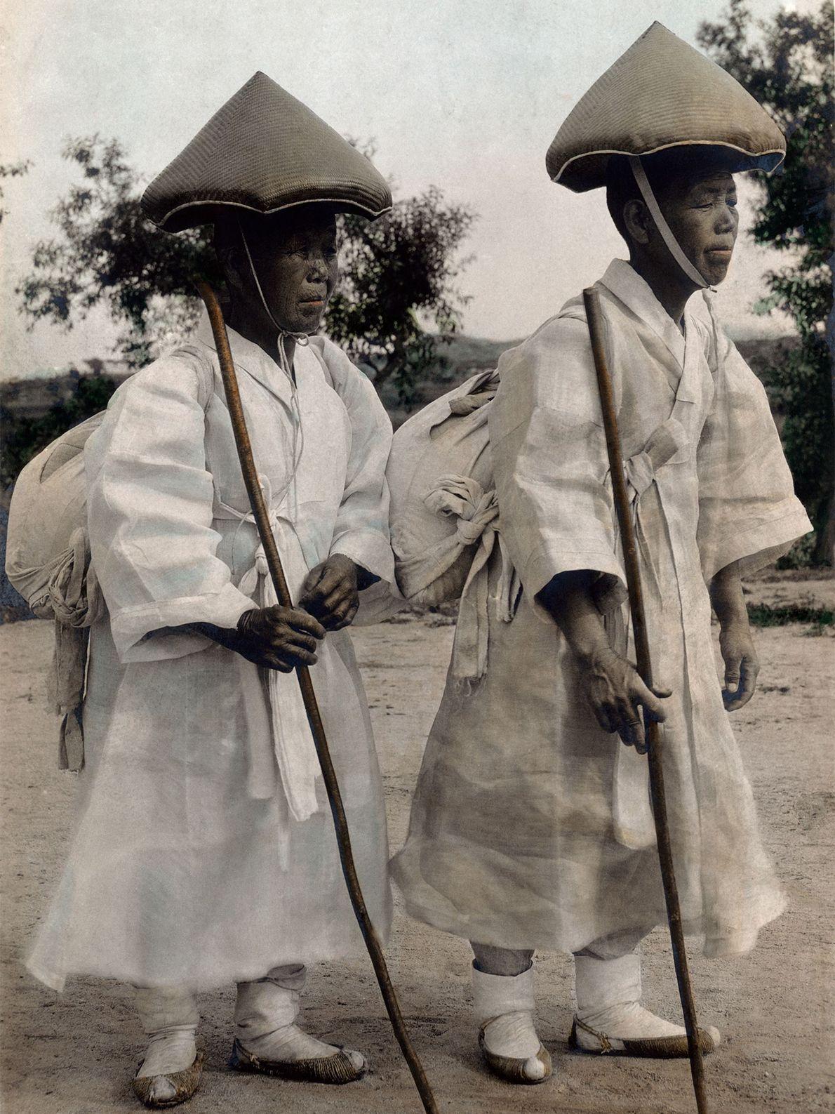 Buddhistische Nonnen Anfang des 20. Jahrhunderts tragen Songnaks auf dem Kopf und laufen mit Wanderstöcken durch ...