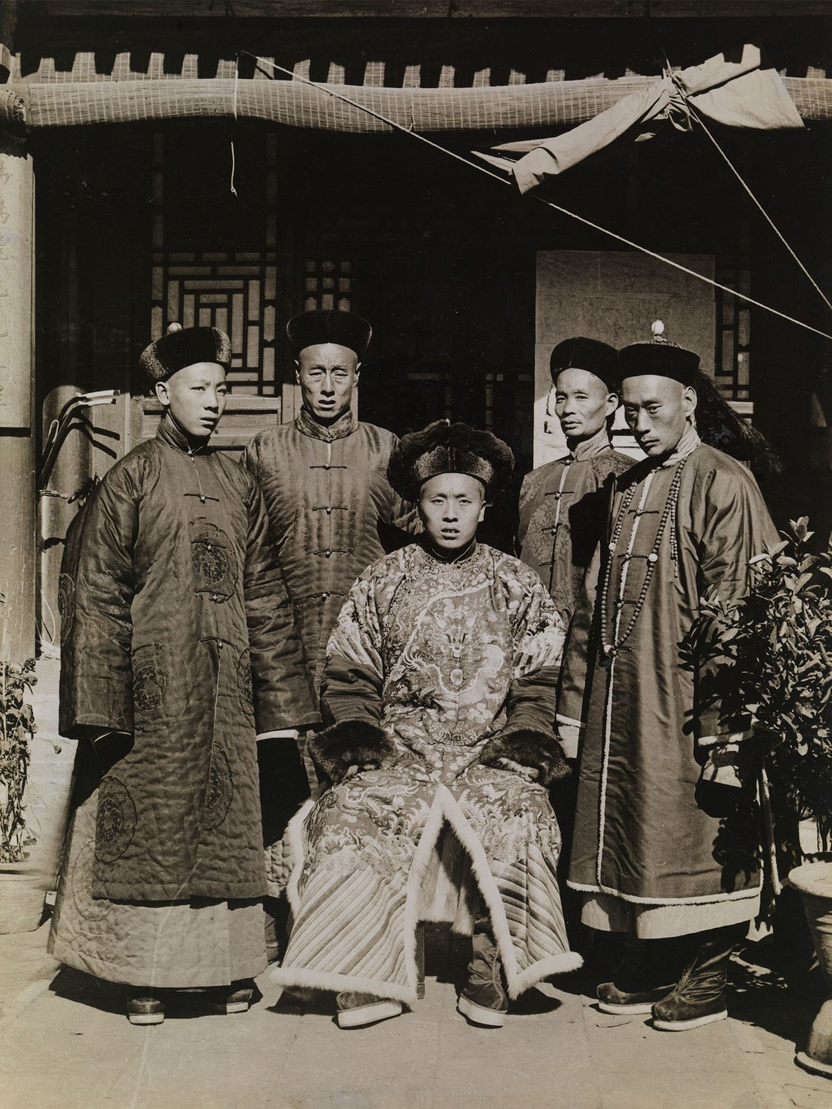 Mandschuren in China tragen elegante Kleidung aus Seide und Pelzhüte, um ihren sozialen Status zu zeigen.