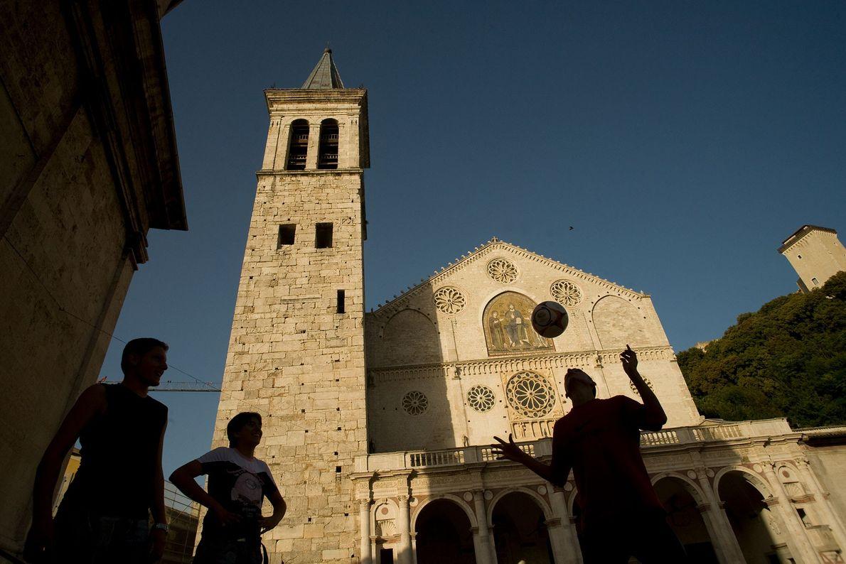Eine kleine Gruppe spielt vor der Cattedrale di Santa Maria Assunta a Spoleto im italienischen Umbrien ...