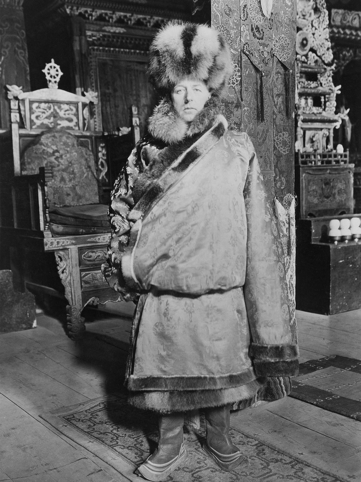 Der Forscher Joseph Rock trägt traditionelle tibetische Kleidung und posiert damit für ein Bild im buddhistischen ...