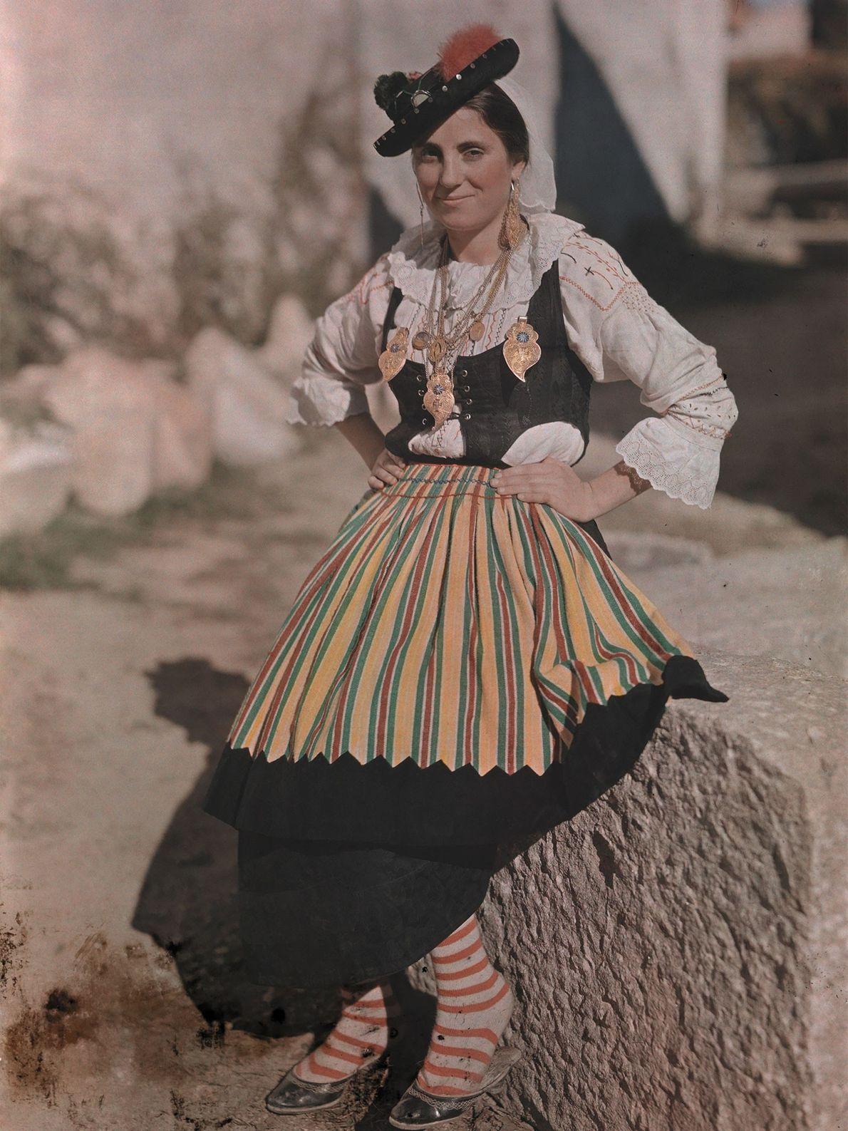 Eine Frau mit festlicher Kleidung und einem schwarzen Hut lehnt sich im portugiesischen Braga an einen ...