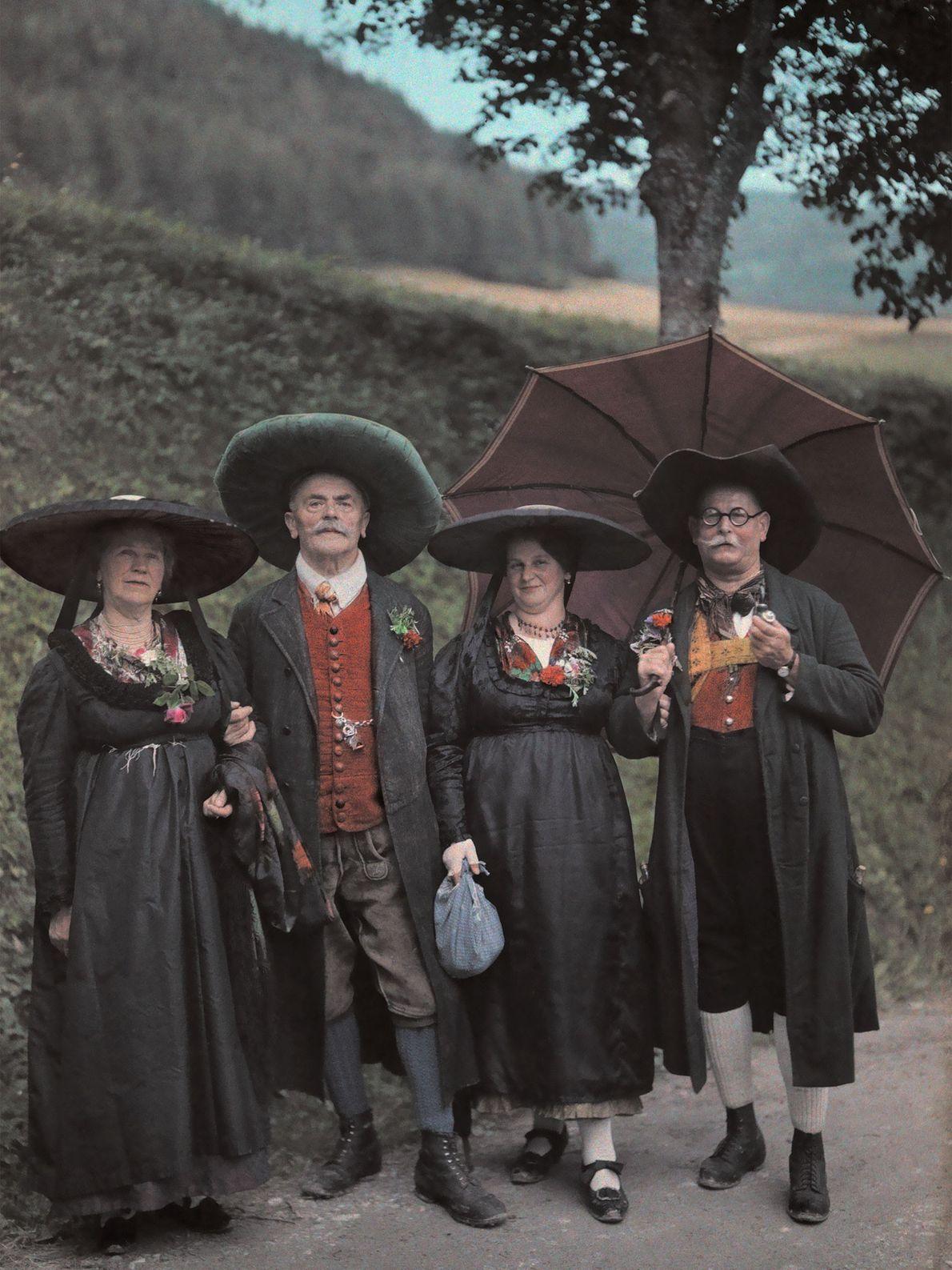 Eine Gruppe Österreicher mit breitkrempigen Hüten läuft in traditioneller Kleidung auf einer Landstraße in der Steiermark.