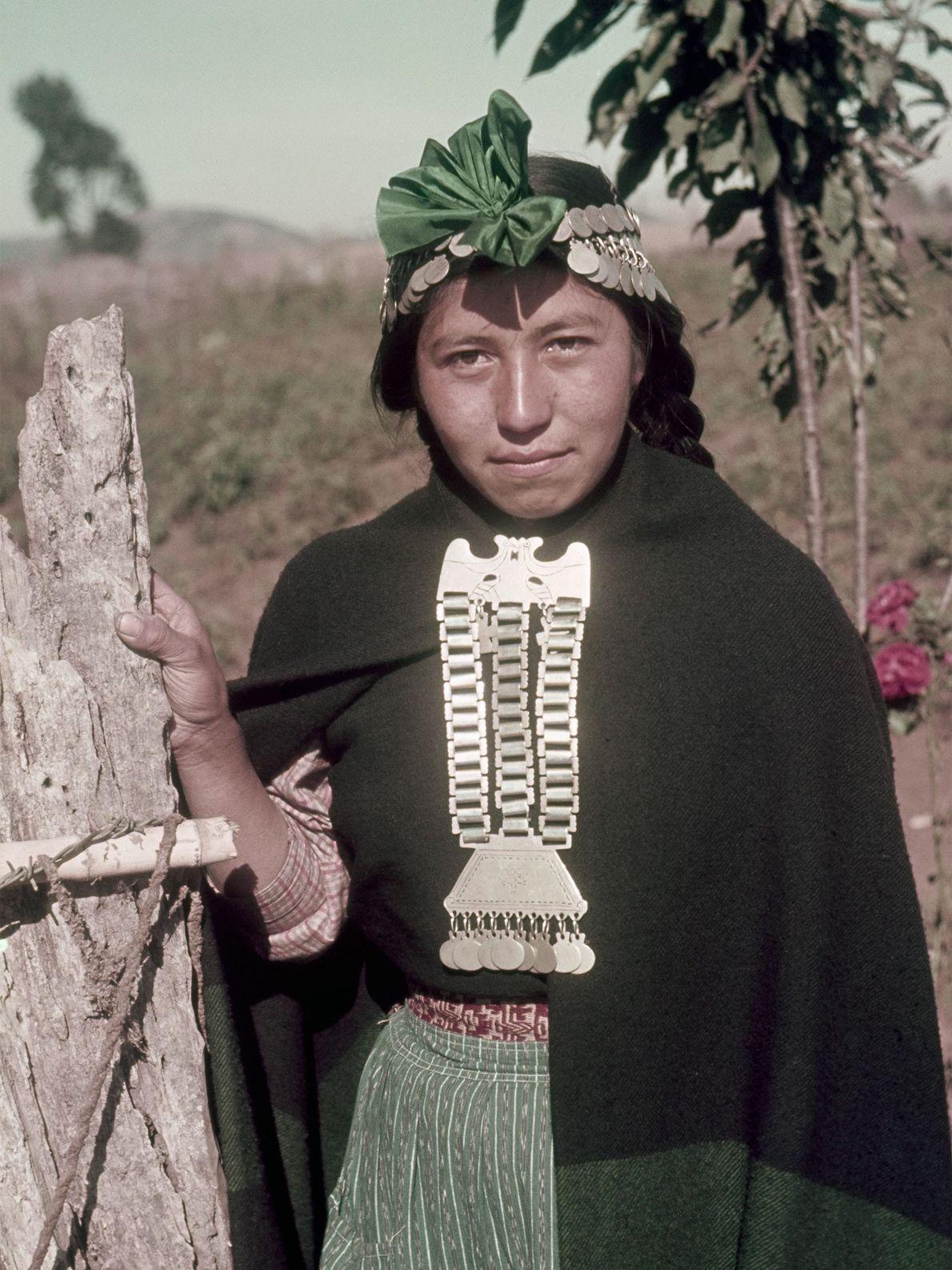 Eine Mapuche aus Chile trägt fein gearbeiteten Silberschmuck an ihrer Kleidung und ihrer Kopfbedeckung.