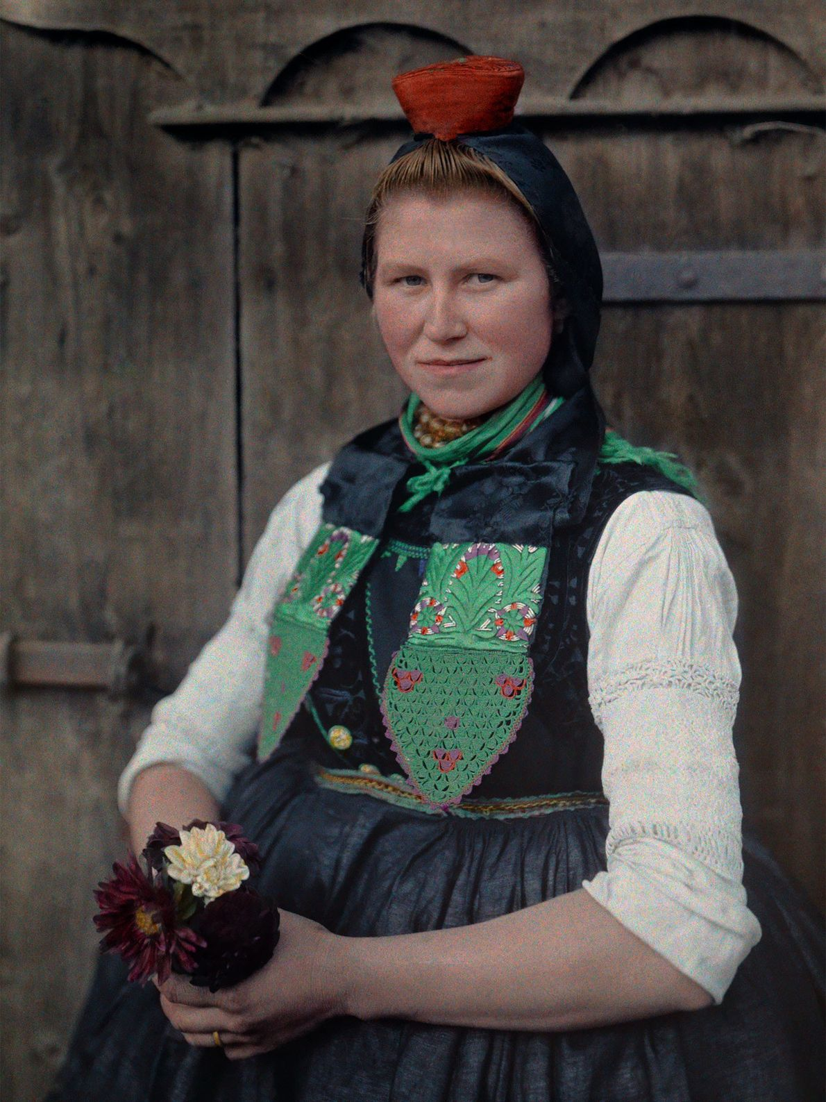 Eine Frau in Schwälmer Tracht hält Blumen in den Händen.