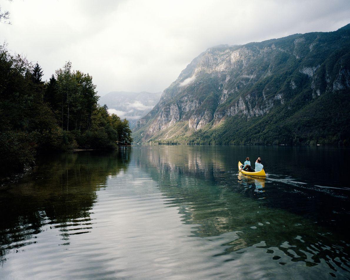 Die deutschen Touristen Julia und Ralph paddeln auf den Bohinj hinaus. Zwischen ihnen im Boot sitzt ...