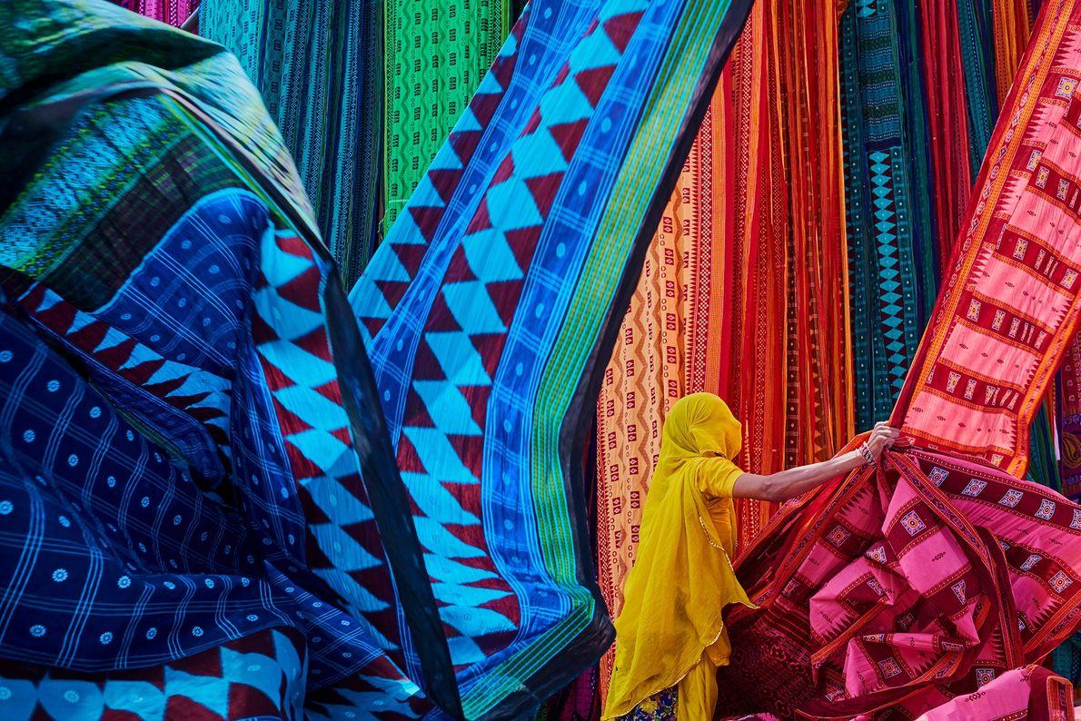 In der Sari-Produktionsstätte in Rajasthan hängen Arbeiterinnen frisch gefärbte Textilien in der Sonne zum Trocknen auf, ...