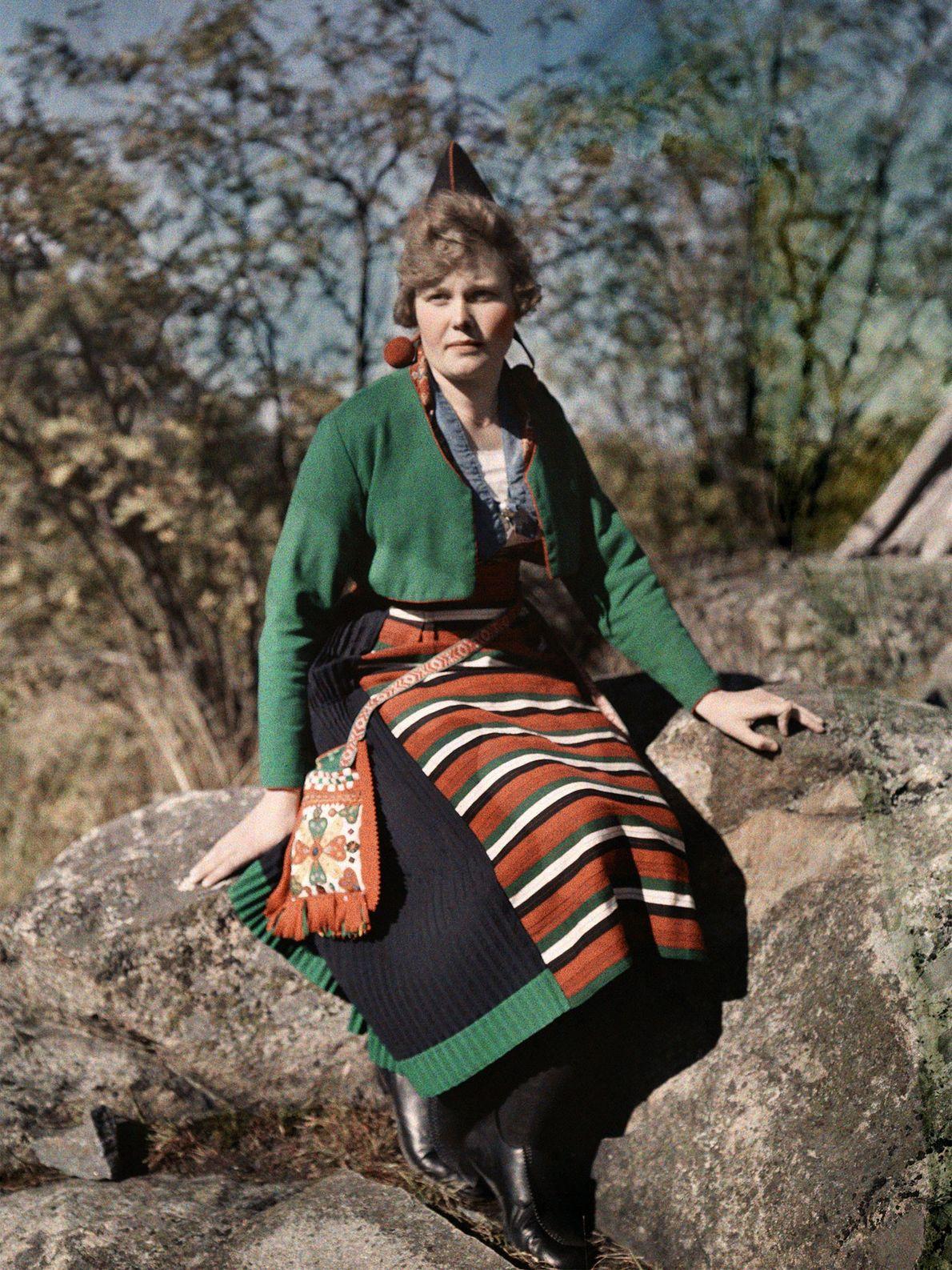 Eine Frau aus Rattvik in Schweden posiert auf einem Felsen im Wald. Sie trägt einen kleinen ...