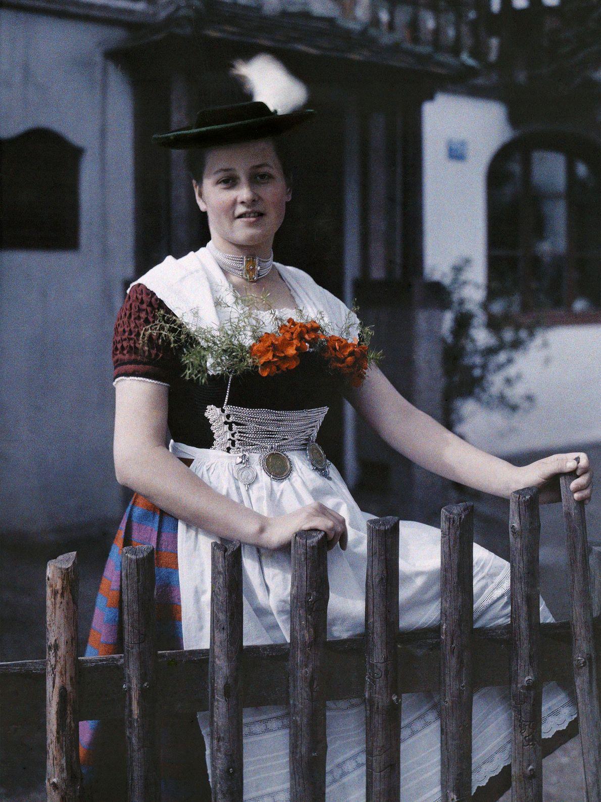 Eine bayerische Frau posiert für ein Bild an einem Zaun im Vorgarten eines Hauses in Deutschland. ...