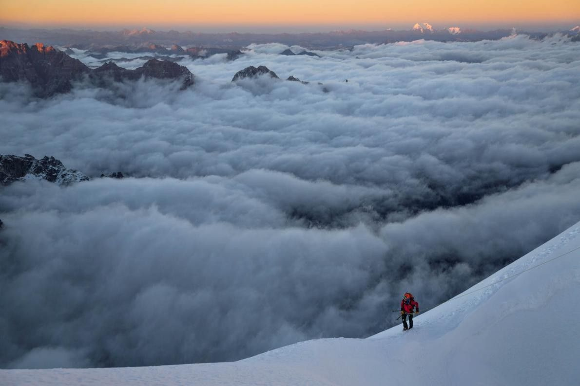 Bergsteiger über Wolkenmeer