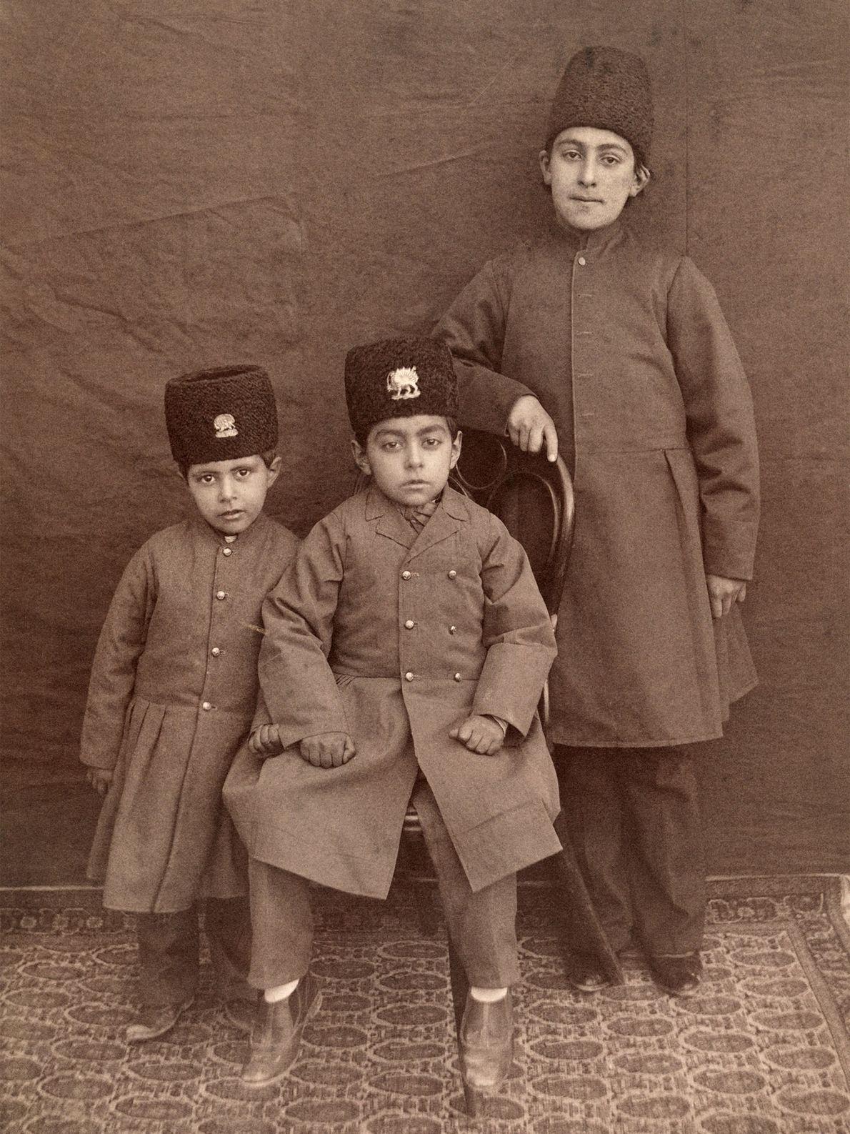 Drei persische Jungen in traditioneller Kleidung und Hüten posieren für ein Porträt.